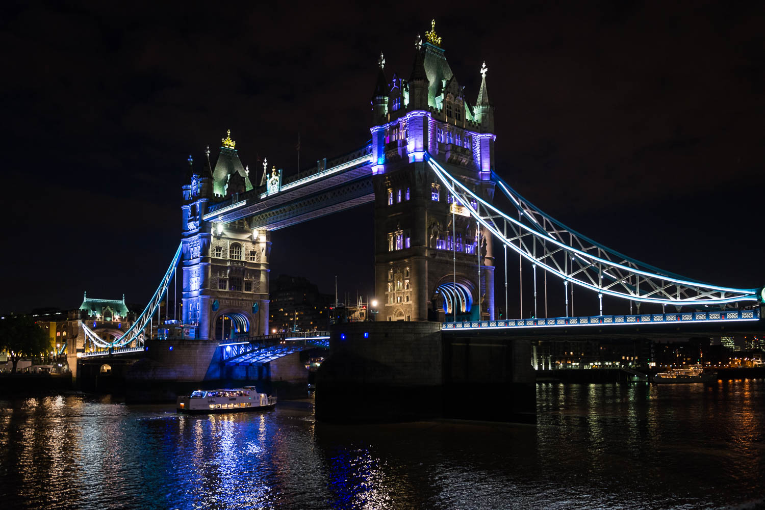 Tower Bridge at Night as a boat travels under the bridge on the River Thames